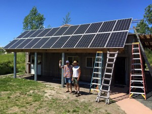 Bruce Cage of EcoDepot and Steve Streets of DayStar Construction stand triumphantly in front of the Waxwing after installing brand new solar panels.